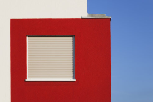Germany, Cologne Widdersdorf, red-white facade of multi-family house with closed window - GWF003550