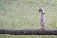 Germany, Bavaria, Girl is balancing on tree trunk - MW000054