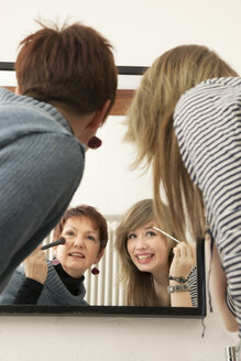 Germany, Berlin, Mother and daughter applying make up - MMFF000018