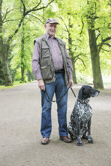 Senior man with his German Shorthaired Pointer in city park - JATF000753