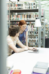Two students in a university library using laptop - WESTF019715