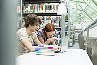 Two students with laptop in a university library - WESTF019717