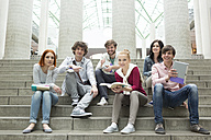 Group of students with books sitting on stairs - WESTF019759