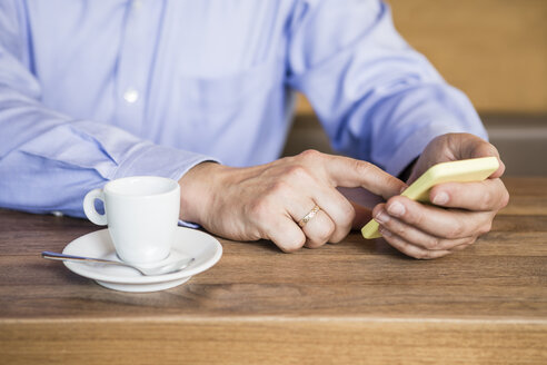 Businessman in cafe using cell phone, close-up - DISF000868