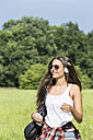 Portrait of smiling young woman with headphones and sunglasses - DRF000700