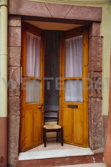 Italy, Sarinia, Bosa, Old door, Ajar with chair - MBEF001044