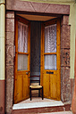 Italy, Sarinia, Bosa, Old door, Ajar with chair - MBEF001044