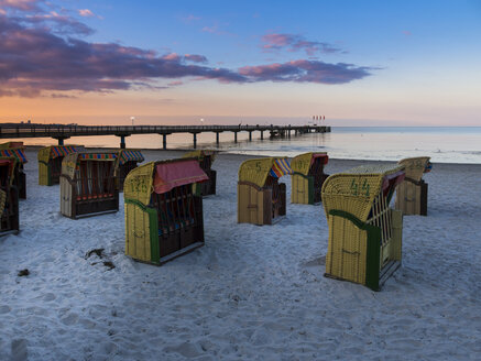 Germany, Schleswig-Holstein, Scharbeutz, Sea bridge, Roofed wicker beach chairs at beach in the evening - AMF002467