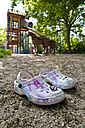 Little girl's shoes standing at playground - JFE000411