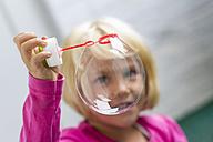 Portrait of little girl making soap bubble - JFEF000433