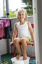Portrait of little girl taking foot bath on balcony - JFEF000437