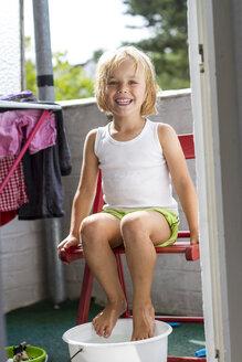 Portrait of little girl taking foot bath on balcony - JFEF000437