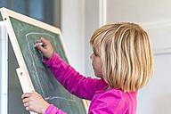 Little girl painting with crayon on blackboard - JFEF000455