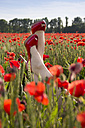 Feet of woman with red pumps in poppy field - YFF000190