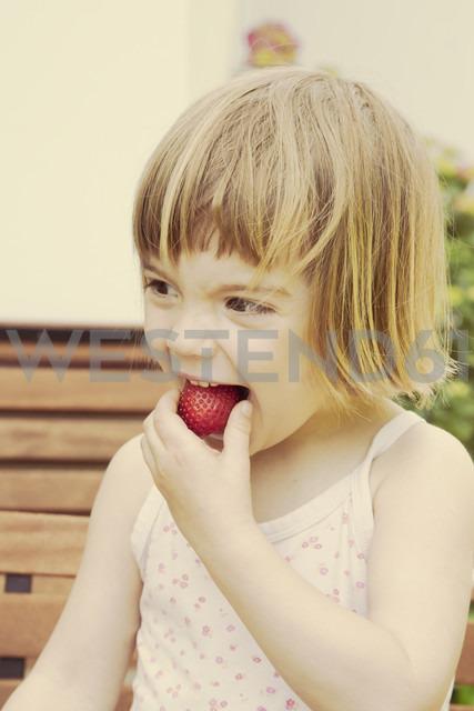 Portrait of little girl eating strawberry - LVF001484
