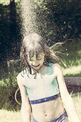 Little girl taking a shower in the garden - LVF001489