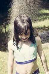 Little girl taking a shower in the garden - LVF001490