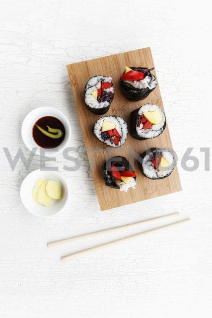 Futo Maki with mango and bell pepper on wooden board, dipping bowls and chop sticks - EVG000653