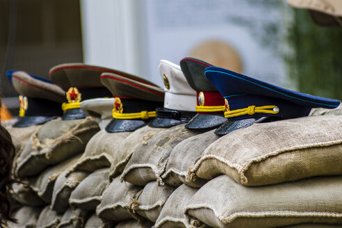 Germany, Berlin, view to row of uniform caps lying on sand bags at Checkpoint Charlie - BIG000010