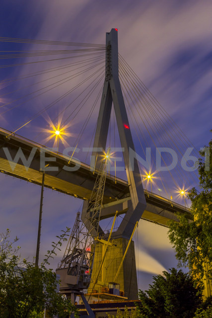 Germany, Hamburg, A Pillar of the Koehlbrand Bridge with a historic crane in the port of hamburg - NKF000164