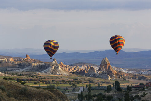 Turkey, Eastern Anatolia, Cappadocia, two hot air balloons hoovering over tuff rock formations at Goereme National Park - SIEF005520