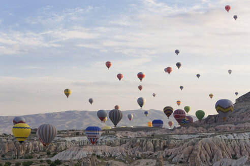 Turkey, Cappadocia, hot air balloons hoovering over tuff rock formations at Goereme National Park - SIE005526