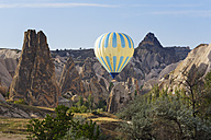 Turkey, Cappadocia, hot air balloon hoovering between tuff rock formations at Goereme National Park - SIE005530