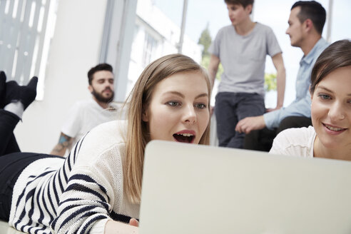 Group of creative professionals using laptop on floor - STKF000932