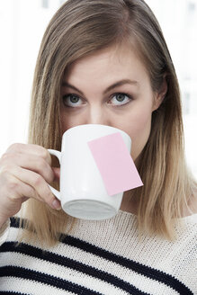 Woman drinking from cup with adhesive note - STKF000979