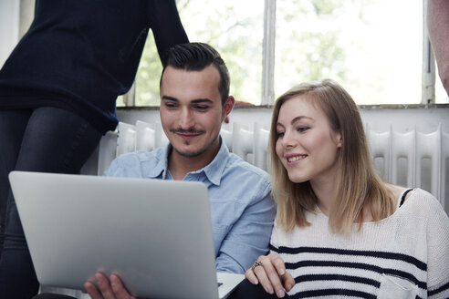 Smiling man and woman using laptop - STKF001015