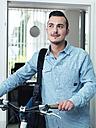 Man pushing bike in office - STKF001003