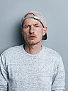 Portrait of man with basecap in front of gray background - STKF000960