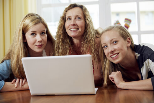 Mother and her two daughters lying on wooden floor at home using laptop - STKF001030