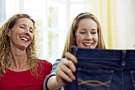 Mother and daughter fitting clothes at home - STKF001038