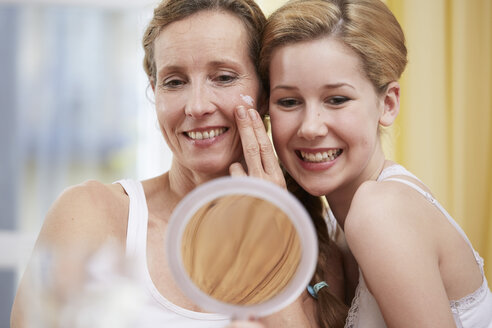 Portrait of mother and daughter heat to head with handheld mirror - STKF001060