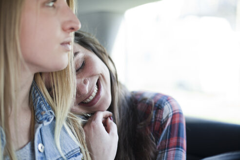 Two young women sitting on back seat of a car - FEXF000087