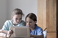 Brother and sister looking at tablet computer at home - SGF000821