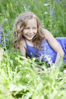 Portrait of smiling girl lying on flower meadow - MAEF008559
