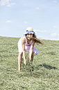 Germany, Bavaria, Young girl throwing hay - MAEF008575