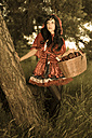 Red Riding Hood with basket leaning on tree trunk - FCF000277