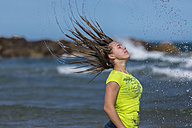 Female teenager tossing her wet hair at waterside of the beach - STSF000430