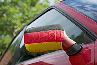 Germany, North Rhine-Westphalia, Mirror cover with German flag on a red car - HAWF000362