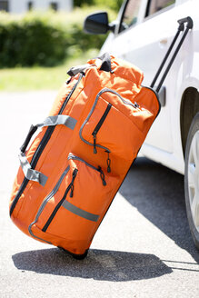 Germany, Bavaria, Rolling suitcase travelling bag leaning on a car - MAEF008587