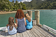 New Zealand, South Island, Marlborough Sounds, Tennyson Inlet, mother with two kids sitting on a wooden jetty - SHF001541