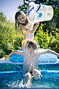 Girl splashing water on brother in inflatable pool - SARF000704