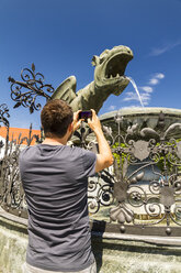 Austria, Klagenfurt, Man taking picture of Lindworm fountain - MBEF001099