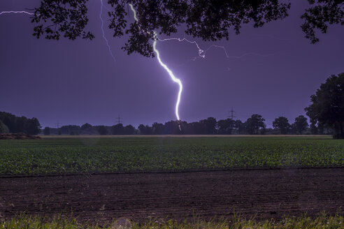 Germany, Lower Saxony, Handorf, lightning strike on the countryside at night - NKF000169