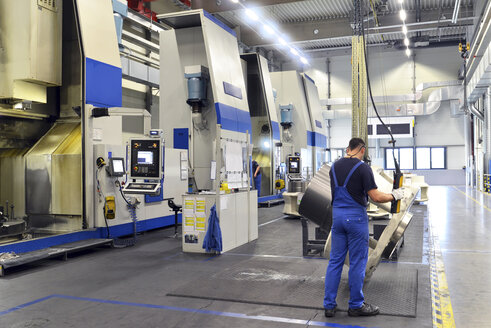 Germany, Saxony, man working at production hall with CNC machines - SCH000334