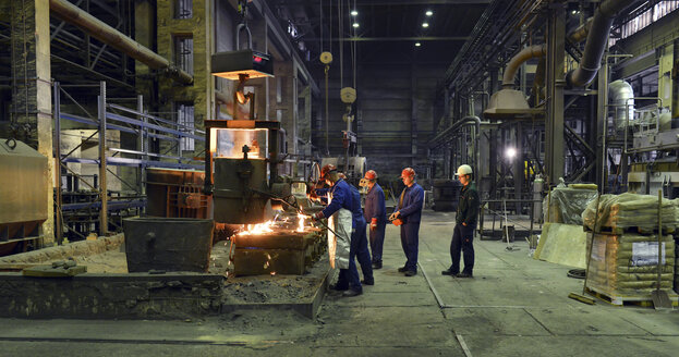 Germany, Saxony, workers racking the blast furnace in a foundry - LY000150