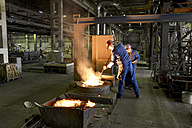Germany, Saxony, workers racking the blast furnace in a foundry - LY000157